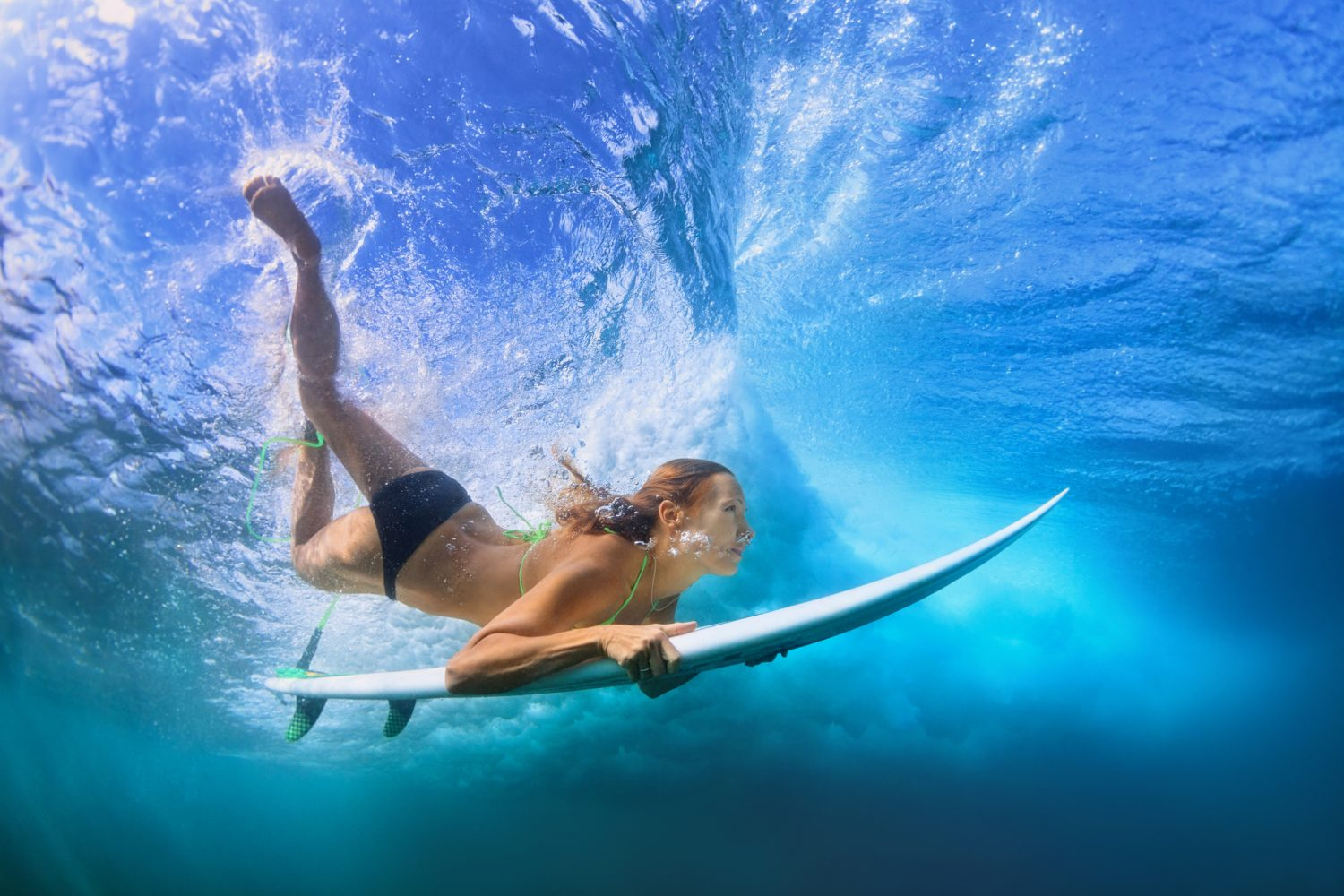 Beautiful surfer girl diving under water with surf board - things to do Maui