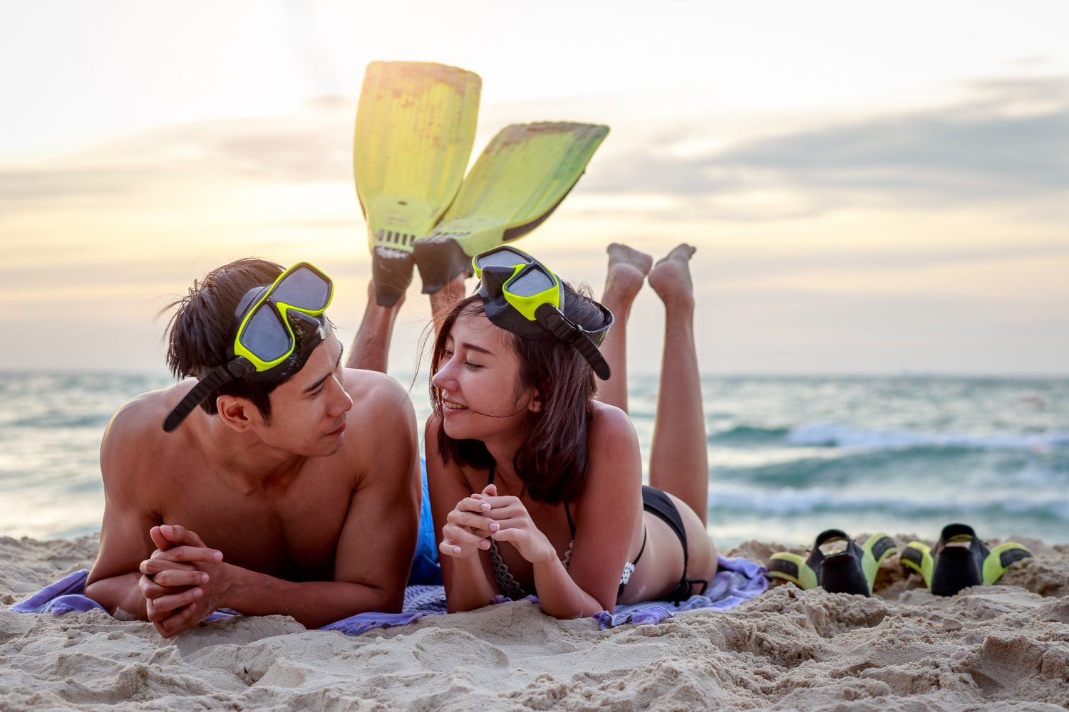 Young Asian happy couple with snorkels and lying on the beach at sunset, Maui Snorkeling