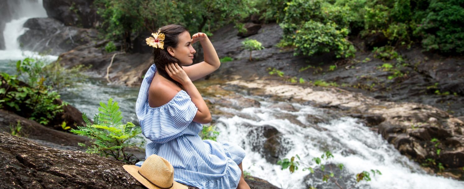 Beautiful girl in a blue dress looks at a Maui waterfall sitting on a rock