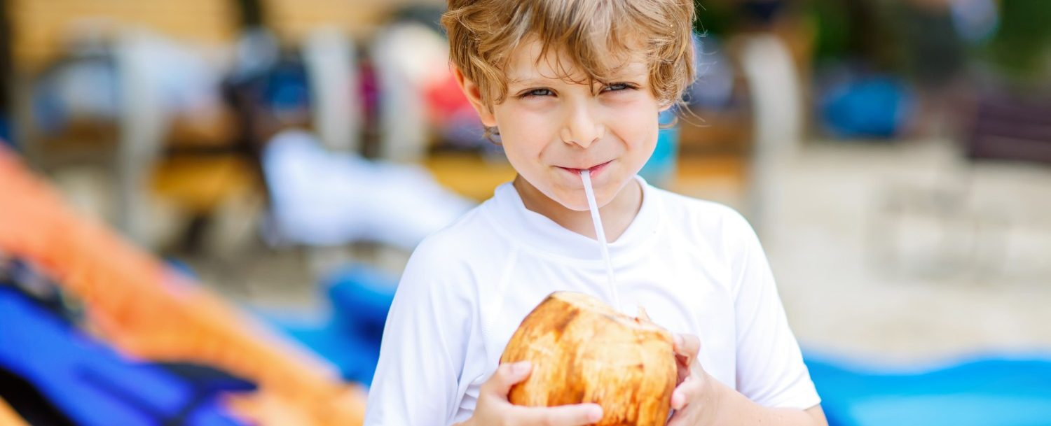 Young boy sipping from a coconut and enjoying the things to do on Maui with kids