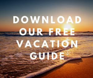 Sunset over ocean with overlaying text of download our free Vacation Guide