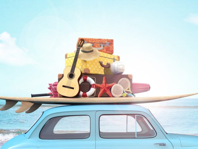 little blue car packed with surf board, guitar and suitcases in front of the ocean for Maui Spring Break