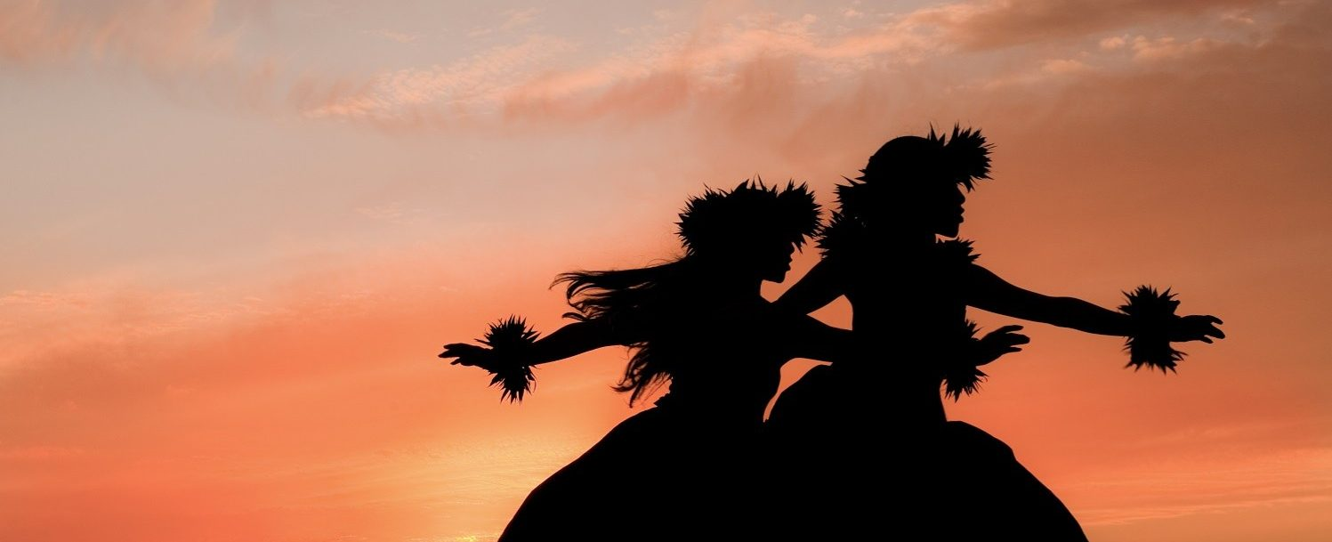 Maui women dancer figures against orange sunset backdrop at a Maui Luau