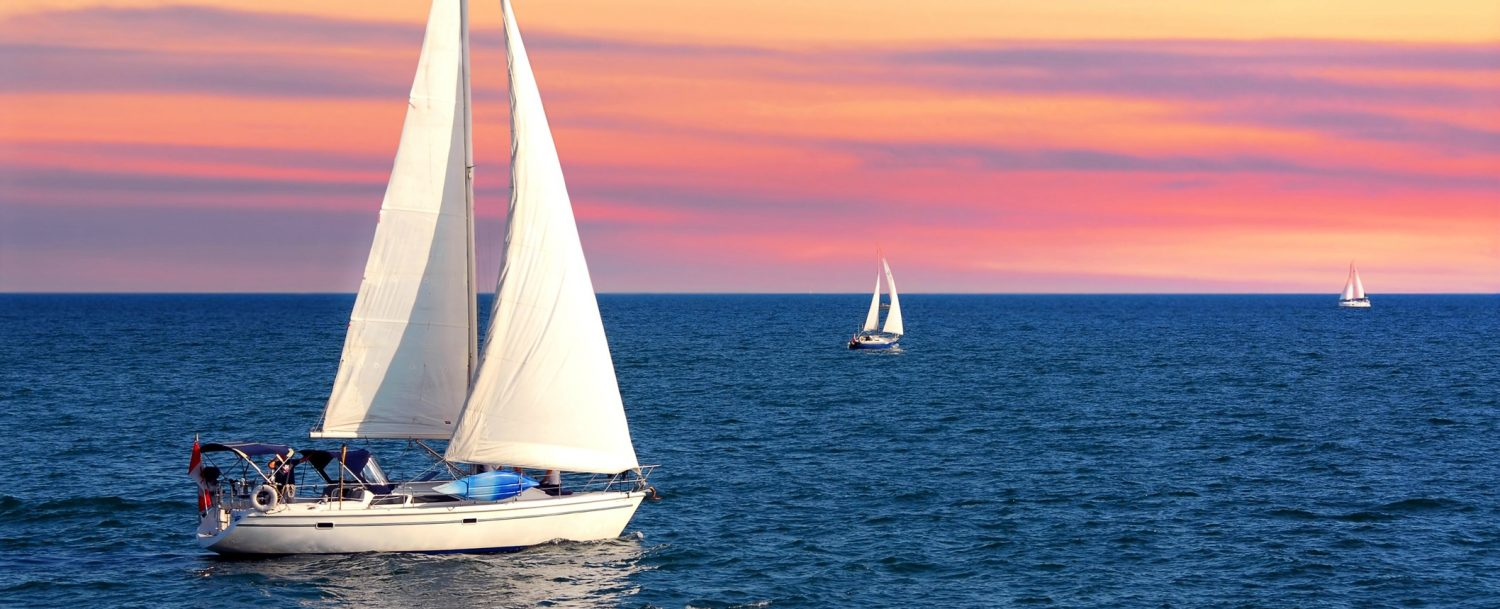 Sailboat sailing towards sunset on a calm evening | Catamaran tours on Maui