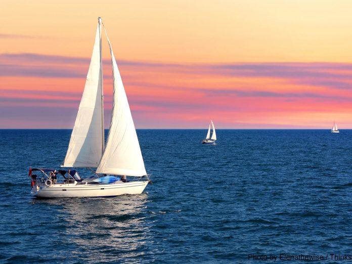 Sailboat sailing towards sunset on a calm evening | Catamaran tours on Maui