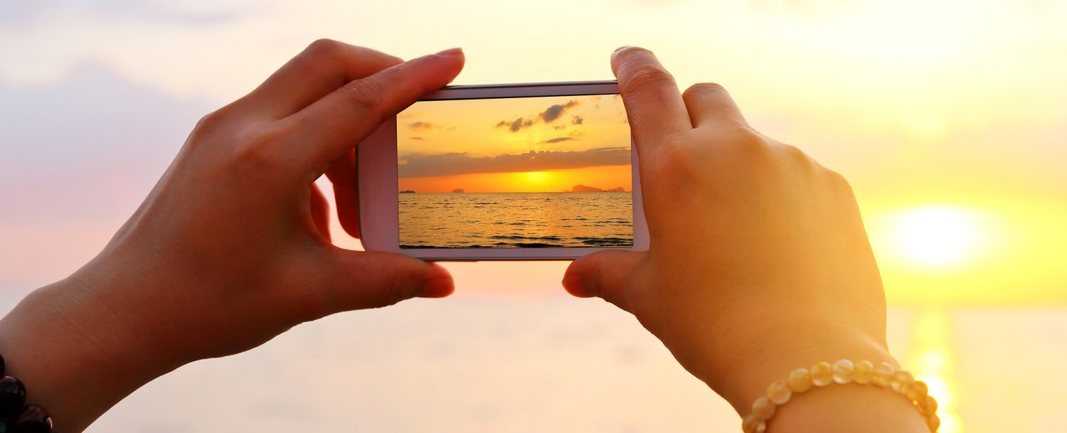 Woman hand using smartphone take a photo on the beach on Maui at sunrise