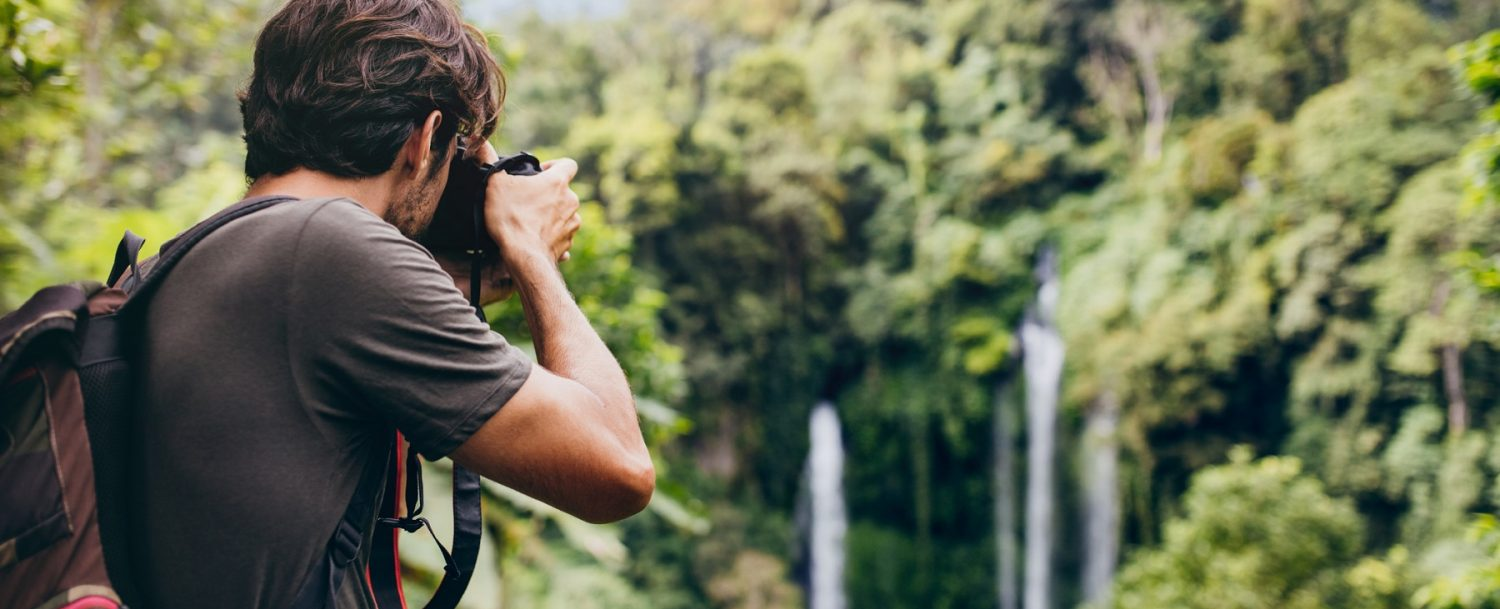 Male hiker photographing a west Maui waterfall in forest