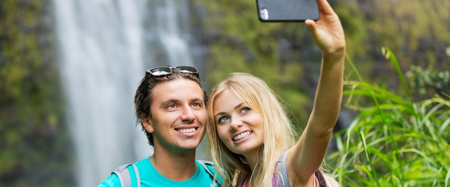 Couple finding the perfect maui selfie spot in front of a waterfall and snapping a picture