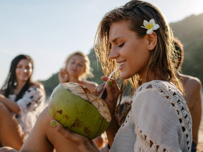 Girl sipping a coconut on Hawaiian Beach | Things to Do on Maui Off the Beaten Path