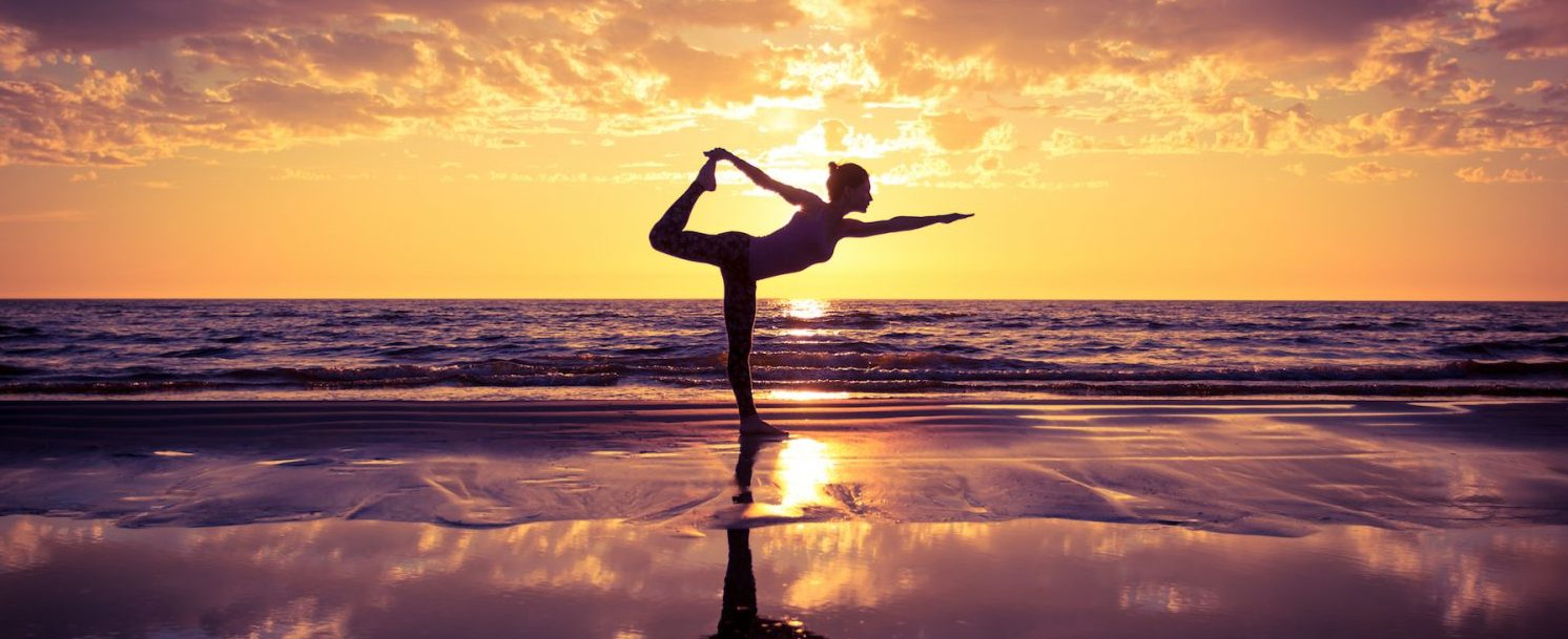 Woman enjoying a Maui yoga retreat on the beachga