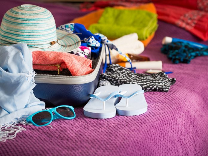 Packing a suitcase with items on our Maui packing list