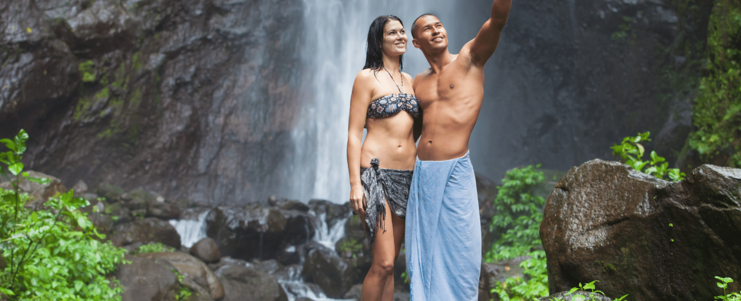Couple standing in front of waterfall smiling